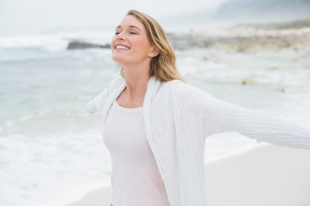 Peaceful casual young woman with eyes closed stretching hands at the beach