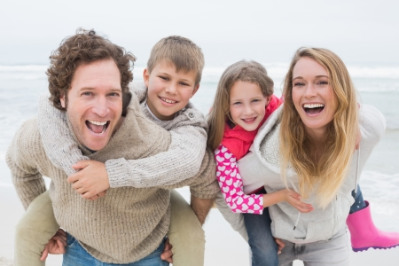 people smiling: Portrait of a happy couple piggybacking their kids at the beach Stock Photo