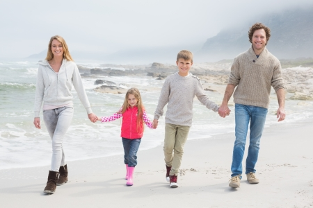 Full length portrait of a happy family of four walking hand in hand at the beach photo