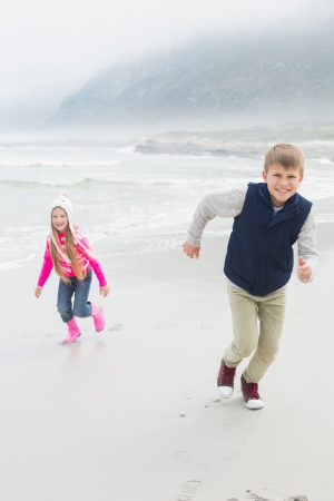 Full length portrait of a happy brother and sister running at the beach photo