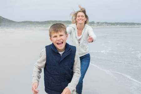 Smiling young woman and cheerful boy running at the beach photo