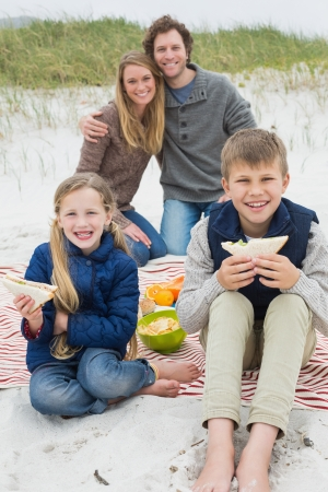 Portrait of a happy family of four enjoying picnic at the beach photo