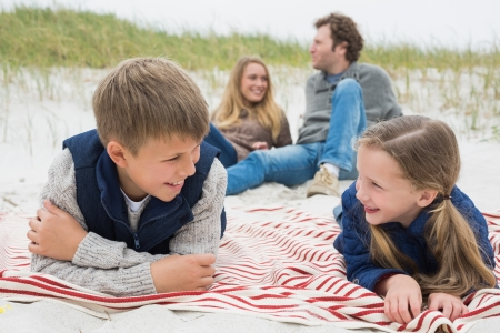Happy siblings lying with parents sitting in background at the beach photo