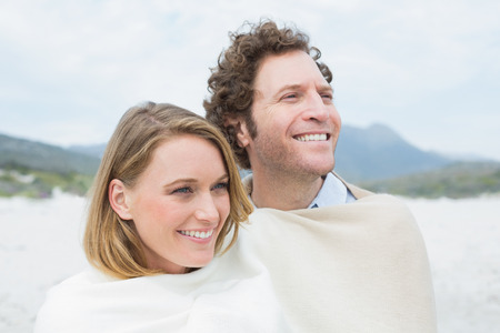 Close-up of a smiling young couple wrapped in blanket at the beach photo