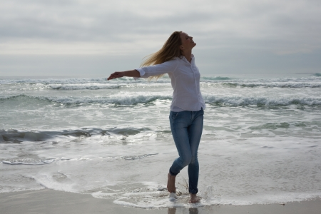 Full length of a casual young woman with eyes closed and arms outstretched at the beach photo