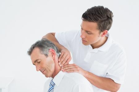 Man chiropractor masseren patiënten nek op witte achtergrond Stockfoto