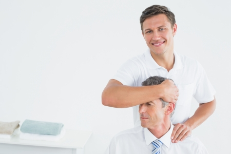Portrait of a male chiropractor doing neck adjustment in the hospital