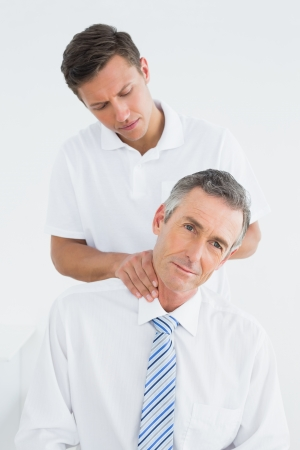 Male chiropractor massaging patients neck over white background photo