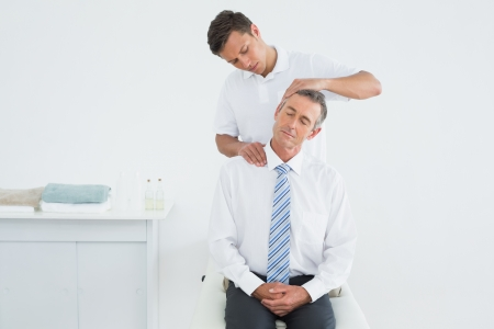 Male chiropractor doing neck adjustment in the hospital