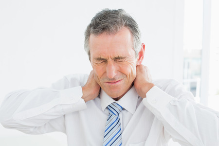Close-up of a mature man suffering from neck pain over white background Foto de archivo