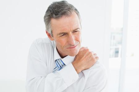 douleur epaule: Close-up d'un homme d'�ge m�r souffrant de douleurs � l'�paule sur fond blanc