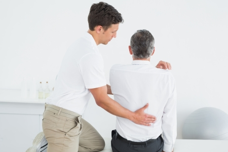 Rear view of a male chiropractor examining mature man at office photo