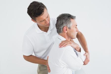 Zijaanzicht van een mannelijke chiropractor onderzoekt volwassen man op een witte achtergrond