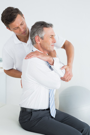 chiropractor: Side view of a male chiropractor examining mature man at office