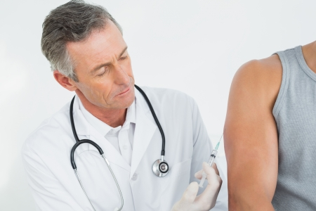 Male doctor injecting a patients arm over white background photo
