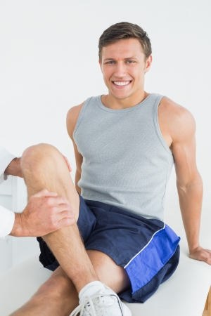 Portrait of a smiling young man getting his leg examined at the medical office photo