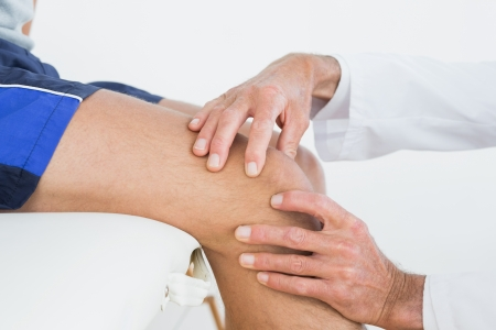 Close-up side view of hands examining patients knee at the medical office
