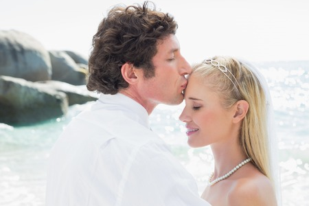 Groom kissing his pretty new wife on forehead at the beach photo