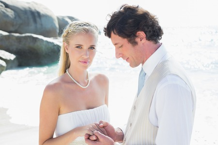 Pretty bride smiling at camera with new husband at the beach photo
