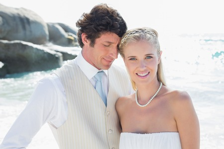 Happy bride and groom embracing at the beach photo