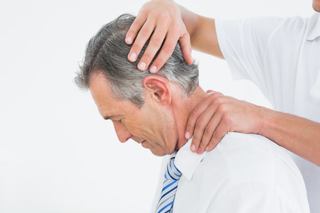 Side view of a chiropractor doing neck adjustment