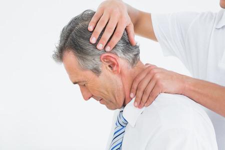 Zijaanzicht van een chiropractor doen nek aanpassing Stockfoto