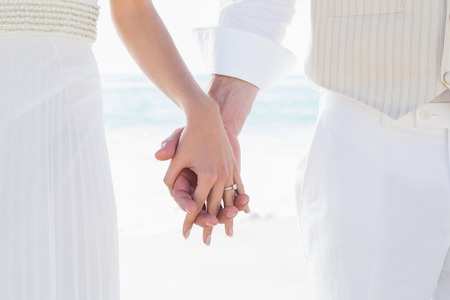 wedding beach: Bride and groom hand in hand at the beach Stock Photo