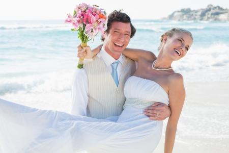 Laughing groom carrying his pretty blonde wife smiling at camera at the beach photo