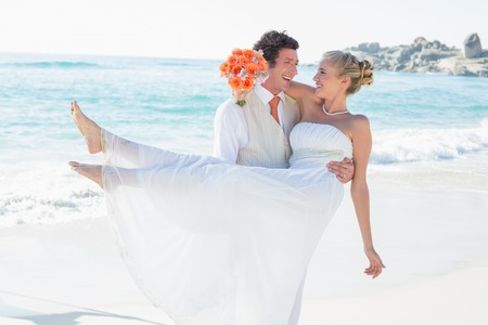 Handsome groom carrying his beautiful blonde wife at the beach Stock Photo