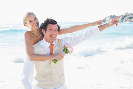 Newlyweds pointing to something smiling at camera at the beach photo