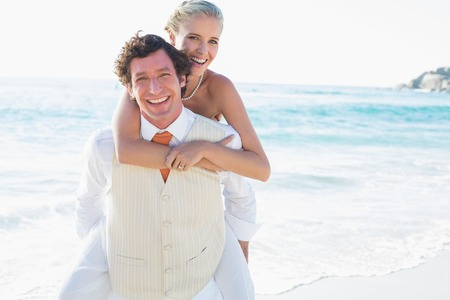 Blonde bride getting a piggy back from new husband at the beach photo