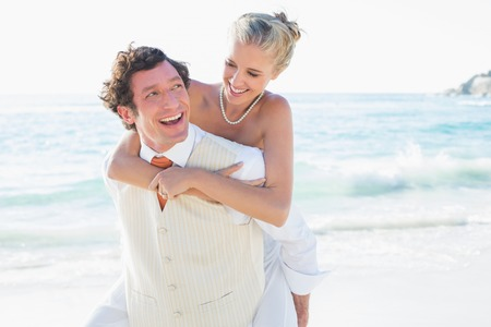 Smiling bride getting a piggy back from new husband at the beach photo
