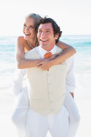 Happy bride getting a piggy back from handsome husband at the beach photo