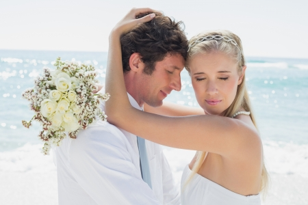 Romantic couple embracing on their wedding day at the beach photo