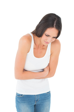 Displeased casual young woman with stomach pain over white background