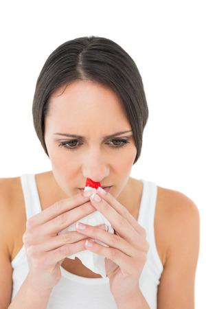 Brunette woman having a nose bleed on white background Foto de archivo