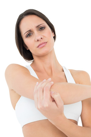 Portrait of a fit young woman with elbow pain over white background photo