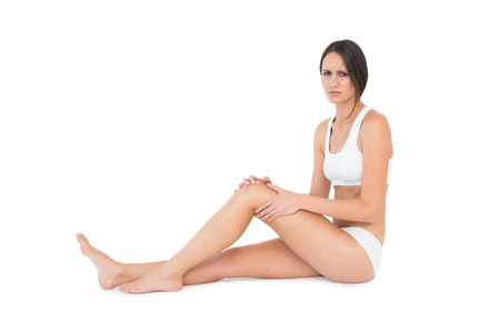 Side view portrait of a fit young woman with knee pain sitting over white background photo