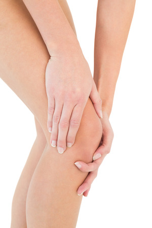 Close-up mid section of a young woman with knee pain over white background photo