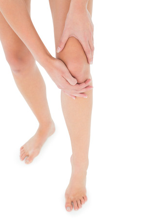 Close-up low section of a fit young woman with leg pain over white background photo