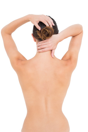 Rear view of a topless young woman suffering from neck ache over white background photo