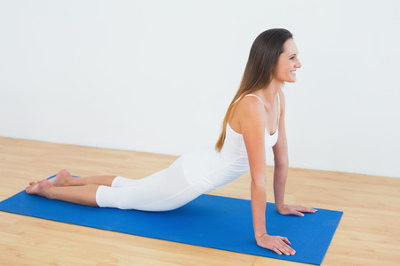 Full length of a fit young woman doing the cobra pose in fitness studio photo