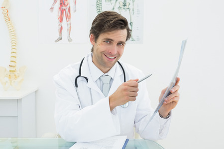 Portrait of a smiling male doctor with x-ray in the medical office photo
