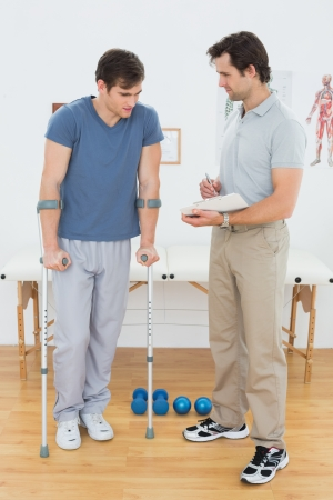 Full length of a male therapist discussing reports with a disabled patient in the gym at hospital photo
