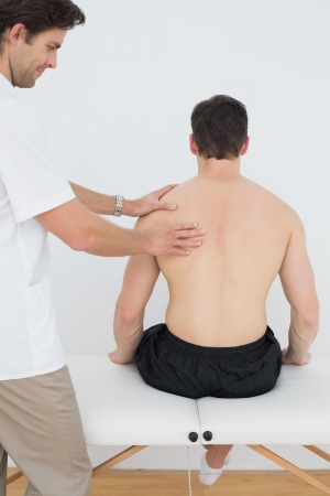 Rear view of a shirtless man being massaged by a physiotherapist in the medical office photo