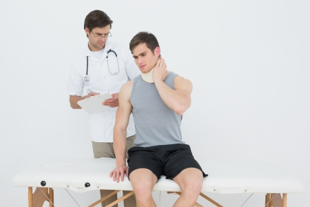 Male doctor listening to patient with concentration at the medical office photo