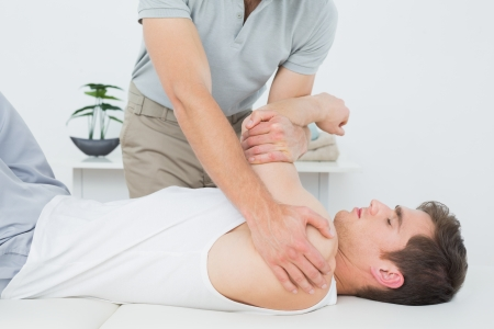 Male physiotherapist examining a young mans hand in the medical office photo