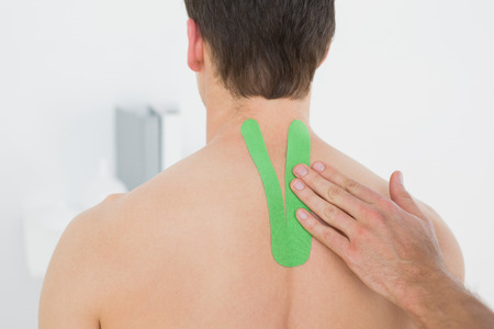 Close-up of a physiotherapist putting on green kinesio tape on patients back in the medical office