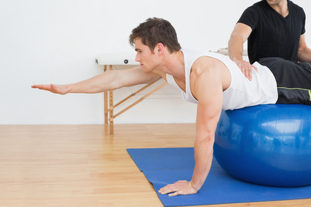 physiotherapist: Physical therapist assisting young man with yoga ball in the gym at hospital Stock Photo