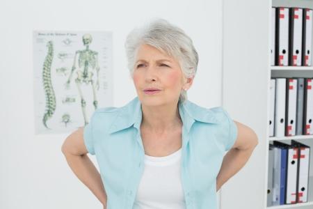 dolor de espalda: Mujer mayor con dolor de espalda de pie en el consultorio m�dico